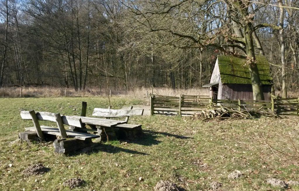 Rastplatz mit Holztischen und -bänken vor einem Schafstall am Ortolan-Wanderweg